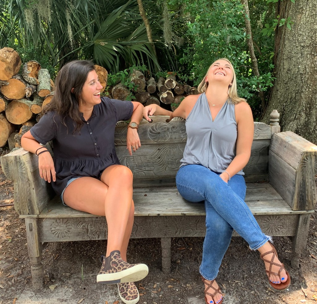 Emily and Ellie (left to right) sit on a bench in Ellie's parents' backyard in front of a woodpile. Emily is wearing a grey button-up shirt, denim shorts, and leopard-print shoes. Ellie is wearing a light grey shirt, jeans, and sandals. Emily is a white woman with dark hair and is turned towards Ellie, laughing. Ellie is a blonde white woman who has her head turned back, also laughing.